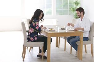 ダイニングテーブルで食事を楽しむ男性と女性の写真素材 [FYI02971127]