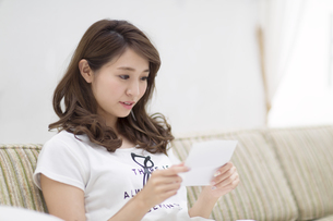 ソファに座って手紙を読む女性の写真素材 [FYI02971129]