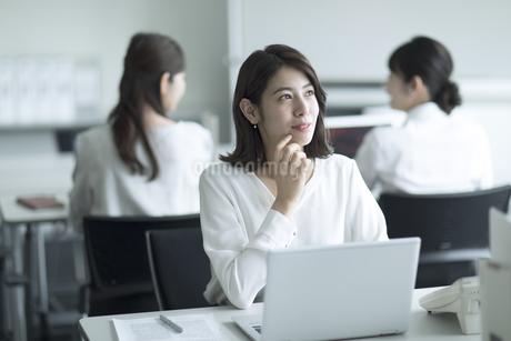 パソコンの前で遠くを見るビジネス女性の写真素材 [FYI02971142]