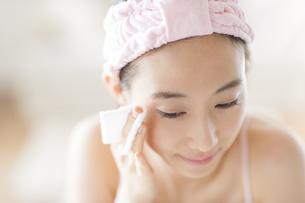 頬にコットンをあてスキンケアをする女性の写真素材 [FYI02971143]