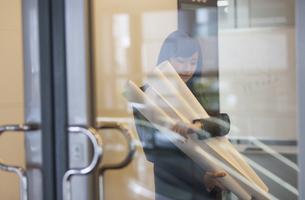 封筒と筒を持って時計を見るビジネス女性の写真素材 [FYI02971144]