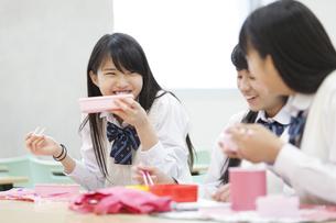 教室でお弁当を食べながら笑う3人の女子高校生の写真素材 [FYI02971160]