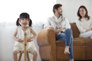 木馬に乗って微笑む女の子とソファーに座る男性と女性の写真素材 [FYI02971167]