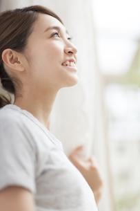 カーテンの傍で微笑む女性の写真素材 [FYI02971173]