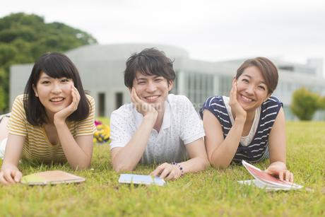芝の上で頬づえをついて笑う学生たちのポートレートの写真素材 [FYI02971186]