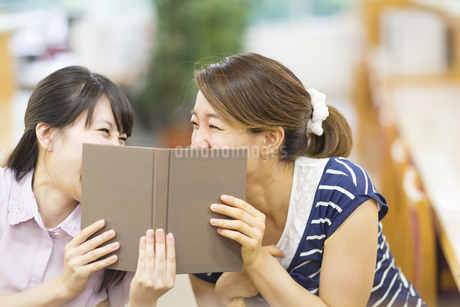 図書室で本で顔を隠して笑う2人の女子学生の写真素材 [FYI02971187]
