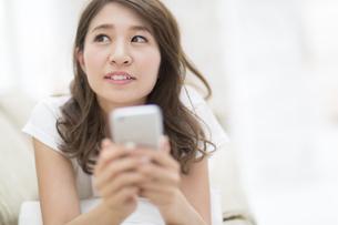 ソファの上でスマートフォンを持って上を見上げる女性の写真素材 [FYI02971189]