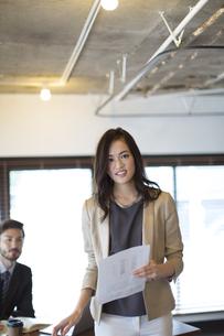オフィスで資料を手に持ち微笑むビジネス女性の写真素材 [FYI02971196]