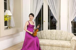 ドレスアップしてバイオリンを持つ女性の写真素材 [FYI02971200]
