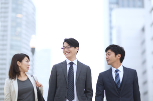 街中で歩きながら会話をするビジネス男女の写真素材 [FYI02971204]