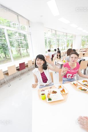 学食で手を振る女子学生の写真素材 [FYI02971206]