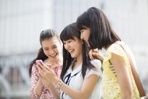 スマートフォンを見つめて喜ぶ3人の若い女性の写真素材 [FYI02971207]