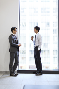 窓際で向かい合って会話をするビジネス男性の写真素材 [FYI02971208]