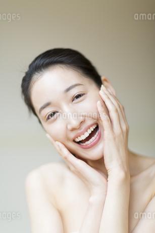 頬に両手を添えた笑顔の女性の写真素材 [FYI02971216]