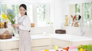 キッチンで花を持つ奥さんの写真素材 [FYI02971218]