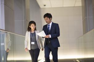 歩きながら打ち合せをするビジネス男女の写真素材 [FYI02971224]