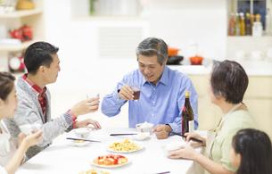 食卓で晩酌をしながら会話をする家族の写真素材 [FYI02971234]