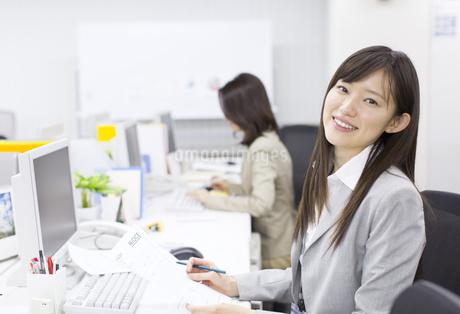 デスクで資料を手に微笑むビジネス女性の写真素材 [FYI02971242]