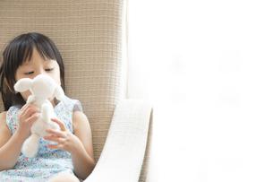 ソファーに座ってぬいぐるみと遊ぶ女の子の写真素材 [FYI02971275]