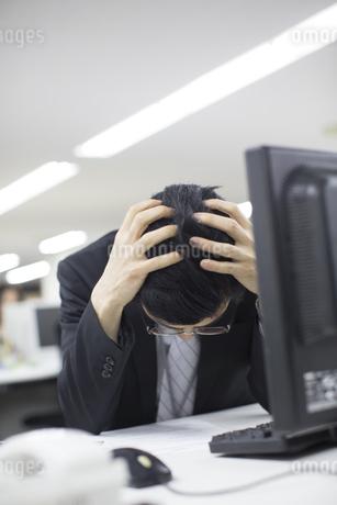 デスクで頭をかかえるビジネス男性の写真素材 [FYI02971290]