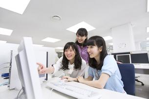 パソコン教室でモニターに向かって微笑む女子学生たちの写真素材 [FYI02971302]