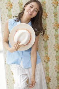 壁に寄り掛かって帽子持って笑う女性の写真素材 [FYI02971303]