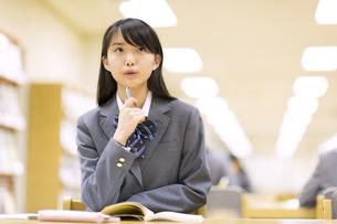 図書室で勉強中に顔を上げる女子高校生の写真素材 [FYI02971304]