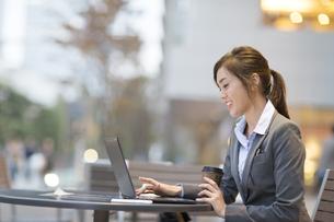 街中でノートPCを操作するビジネス女性の写真素材 [FYI02971305]