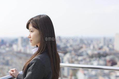 屋上で遠くを見るビジネス女性の写真素材 [FYI02971308]