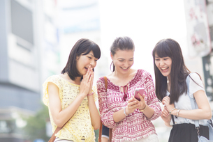 スマートフォンを見つめて喜ぶ3人の若い女性の写真素材 [FYI02971311]