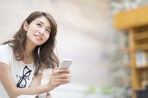 スマートフォンを持って上を見上げる女性の写真素材 [FYI02971316]