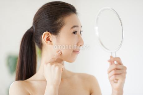 手鏡を見て微笑む女性の写真素材 [FYI02971320]