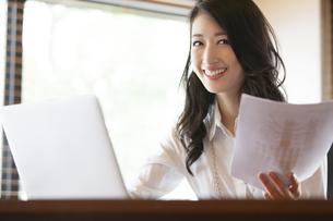オフィスで資料を手に持ち微笑むビジネス女性の写真素材 [FYI02971323]