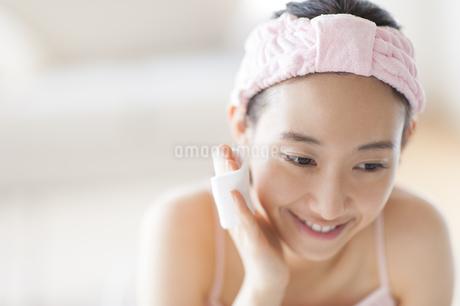 頬にコットンをあてスキンケアをする女性の写真素材 [FYI02971326]
