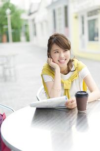 街中で椅子に座って地図を手に持ち微笑む女性の写真素材 [FYI02971327]