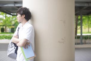 柱にもたれて腕を組む男子学生の写真素材 [FYI02971334]