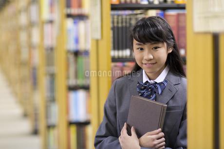 図書室で本を抱える女子高校生の写真素材 [FYI02971335]