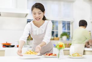 笑顔で食卓に料理を置く若い奥さんの写真素材 [FYI02971343]