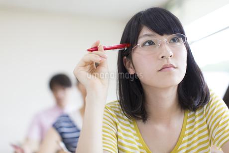 ペンを頭に考える女子学生の写真素材 [FYI02971346]