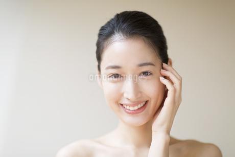 頬に片手を添えて微笑む女性の写真素材 [FYI02971353]