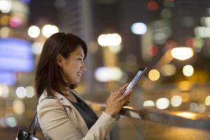夜の街を背景にタブレットPCを見て微笑むビジネス女性の写真素材 [FYI02971358]