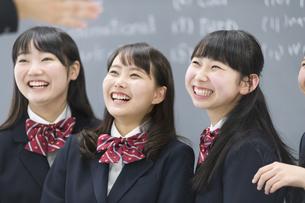 黒板の前で笑う女子学生3人の写真素材 [FYI02971362]