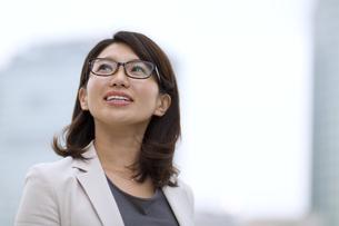 オフィスビルを背景に上を見上げるビジネス女性の写真素材 [FYI02971373]