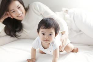 ベッドの上で微笑む赤ちゃんをあやす女性の写真素材 [FYI02971374]