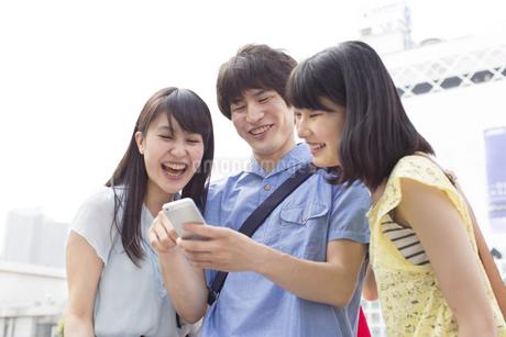 街中でスマートフォンを見て微笑む3人の若者の写真素材 [FYI02971380]