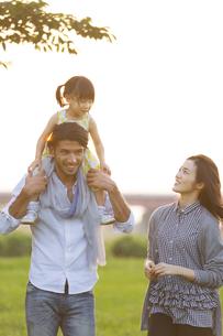 土手を散歩する3人家族の写真素材 [FYI02971388]