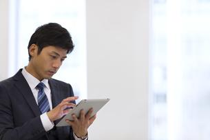 オフィスでタブレットPCを見るビジネス男性の写真素材 [FYI02971393]