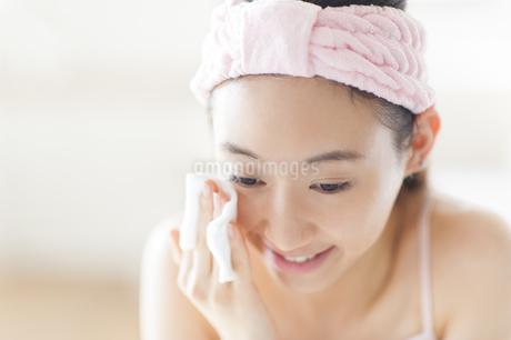 頬にコットンをあてスキンケアをする女性の写真素材 [FYI02971399]