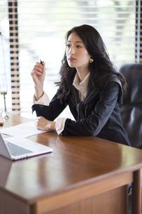 オフィスのデスクで考え込むビジネス女性の写真素材 [FYI02971400]