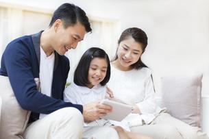 タブレットPCを見ながら笑い合う親子の写真素材 [FYI02971409]